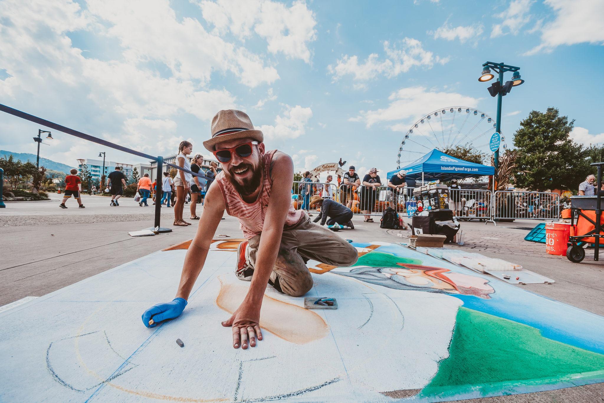 Chalk artist on ground smiling at camera